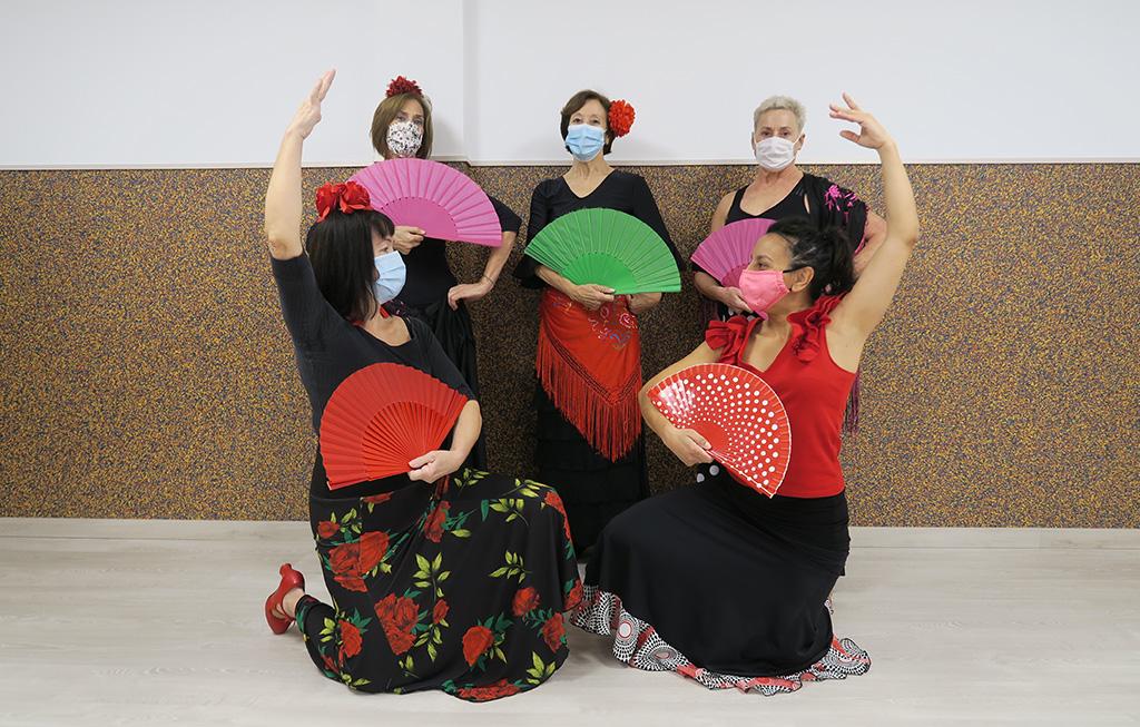 Cinco mujeres con abanicos y vestidos de flamenco