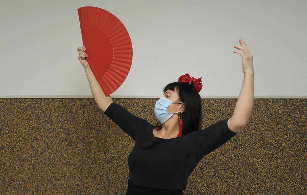 Mujer con abanico haciendo pose de flamenco