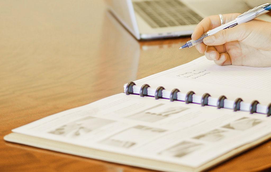 Mano escribiendo en un cuaderno