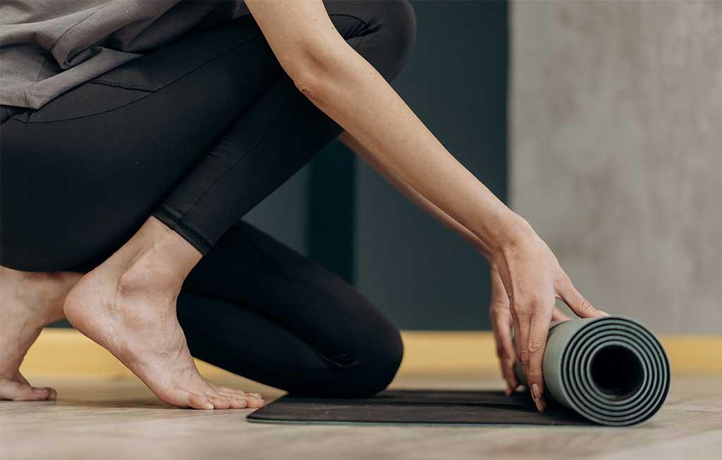 persona desenrollando esterilla de yoga