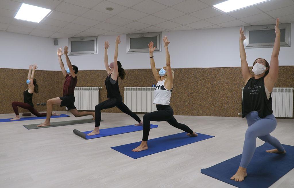 personas realizan saludo al sol en clase de yoga