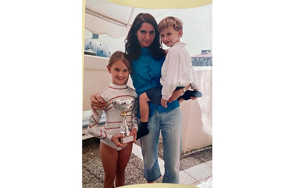 madre con dos hijos, la chica tiene una copa de competición