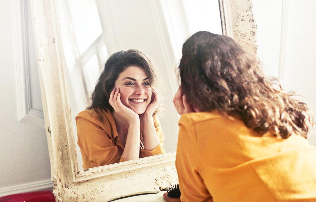 mujer se mira feliz en el espejo